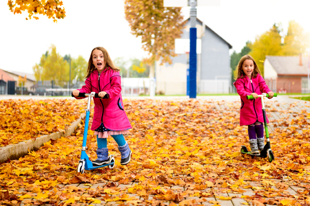 niñas gemelas: Twin girls in pink coat are riding scooter on maple leaves. Active children in sport pursuit is exercising in the nature in the autumn with cold temperatures outside.