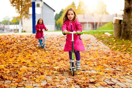 niñas gemelas: niñas gemelas en la capa rosada se monta la vespa en las hojas de arce. Los niños activos en la búsqueda deporte se ejercita en la naturaleza en el otoño con temperaturas frías fuera. Foto de archivo