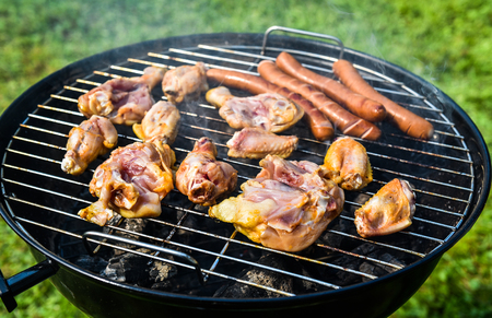 weber: Delicious variety of meat on barbecue grill with char coal. Grilling food on a weber type small cheap BBQ grill at home. Sausages, chicken, and hot dogs in nature.