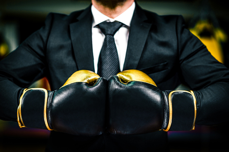 relentless: Businessman with boxing gloves is ready for corporate battle. Man in suit, shirt and a tie is holding combat gloves together. Shot in a boxing gym, concept of relentless struggle and success.