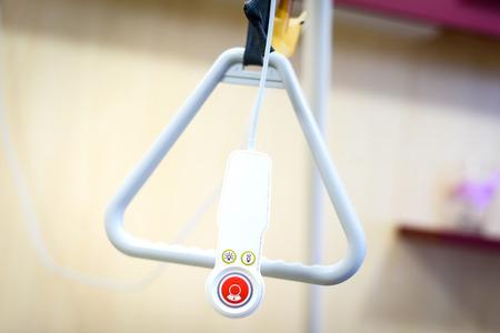 Ziekenhuisbed driehoek handvat met een noodvoorziening afstandsbediening baken. Accessoires in bejaardentehuis helpt oudere of zieke mensen opstaan uit bed of bel de verpleegkundige of een docto