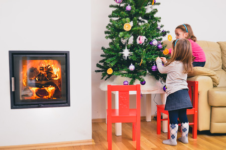niñas gemelas: Children and Christmas tree in modern luxury apartment with fireplace. Twin girls are decorating Christmas tree with hot fire and flames burning in the fireplace.