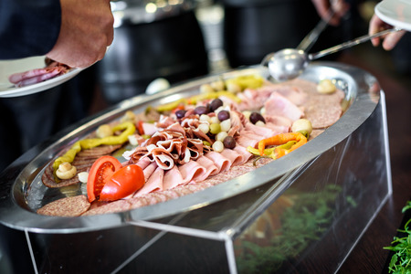 Charcuterie in self service all you can eat buffet plate. Different variety of sliced meat, cheese, prossutto and salami on a banquet or all you can eat restaurant.