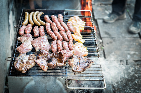 Mixed variety of Meat on barbecue grill with coal. Cevapcici, sausages, chicken wings and hot dogs on charcoal barbecue BBQ.