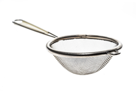 Small metallic tea strainer sieve with handle isolated on white. Modern kitchen utensil for tea or soup filtration. Stock Photo
