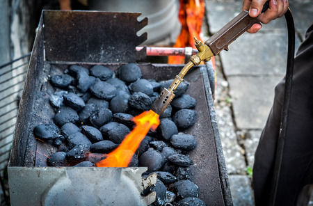 propane: Firing up charcoal briquettes for the BBQ grill. Starting a grill with propane gas torch. Stock Photo