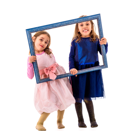 Twin girls are making happy expressions with picture frame. Children posing in studio, fooling around making different facial expressions.