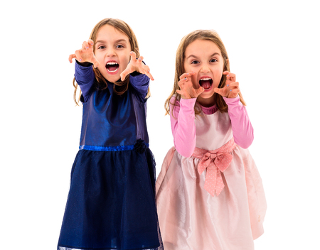 Twin girls are angry, mad and disobedient with bad behavior. Children making the act of insubordination and disobedience, yelling, showing teeth, behaving crazy. Stock Photo