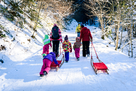 People are pulling sledge on the mountain road in woods. Active family in the winter sports activities with sleigh on snowy sliding forest road.