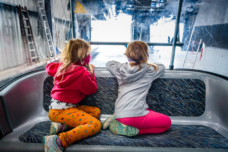 niñas gemelas: Twin girls riding cabin cable car and enjoying the view. Inside of cabin with children looking at the amazing scenery. Krvavec, Slovenia in the summer.