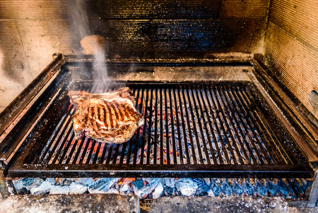 Grilling Big T-bone steak on natural charcoal barbecue grill. Preparing a big steak on natural firewood BBQ in outside fireplace. Stock Photo