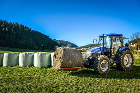 Tractor carrying hay bale rolls - stacking them on pile. Agricultural machine collecting bales of hay on a field in Slovenia.