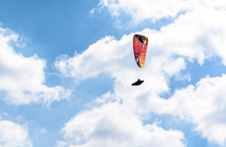 Paraglider flying against the blue sky with white clouds. Parachute on  a clear blue sunny day with sun and clouds. Stock Photo