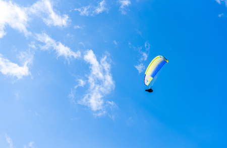 Paraglider flying against the blue sky with white clouds. Parachute on  a clear blue sunny day. Stock Photo