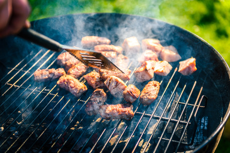 weber: Grilling delicious variety of meat on barbecue charcoal grill. Grilling food on a weber type small cheap BBQ grill at home. Family backyard barbecue - BBQ picnic. Stock Photo