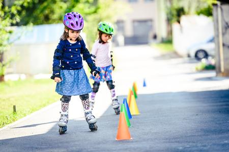 Niños aprendiendo a patinar sobre la carretera con conos. Las niñas gemelas están practicando el patinaje sobre ruedas seguro en una carretera de acceso a casa con equipo de protección - cascos, rodilla, codo y protectores de mano o almohadillas.