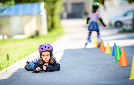 Child fell while learning to roller skate on the road. Twin girls are practising safe roller skating on a home driveway road wearing protective gear - helmets, knee, elbow and hand protectors or pads.