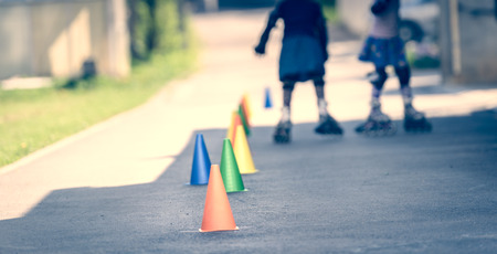 roller blade: Children learning to roller skate on the road with cones. Twin girls are practising safe roller skating on a home driveway road wearing protective gear - helmets, knee, elbow and hand protectors or pads. Stock Photo