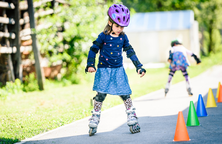 Children learning to roller skate on the road with cones. Twin girls are practising safe roller skating on a home driveway road wearing protective gear - helmets, knee, elbow and hand protectors or pads. Stock Photo