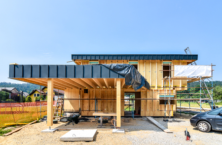 Building energy efficient passive wooden house. Construction site and exterior of a wooden panel house with scaffolds ready for wall insulation.