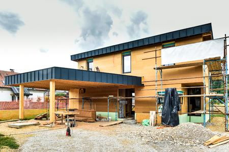 Energiezuinig passief houten huis bouwen. Bouwplaats en buitenkant van een houten paneelhuis met steigers klaar voor muurisolatie. Stockfoto