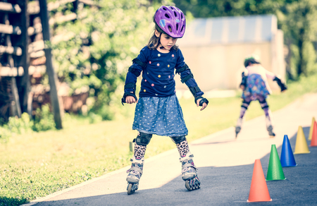 child protection: Children learning to roller skate on the road with cones. Twin girls are practising safe roller skating on a home driveway road wearing protective gear - helmets, knee, elbow and hand protectors or pads. Stock Photo