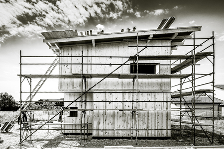 scaffolds: Building energy efficient passive wooden house. Construction site and exterior of a wooden panel house with scaffolds ready for wall insulation.