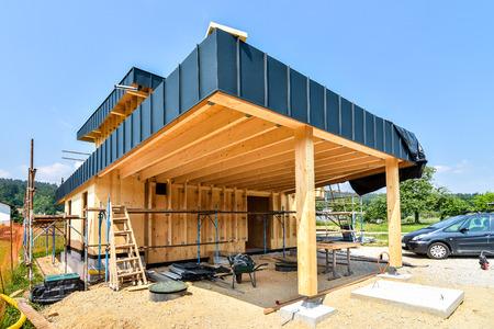 建物エネルギー効率的な受動的な木の家。建設現場、足場の壁の絶縁材の準備と木製パネルの家の外観。 写真素材
