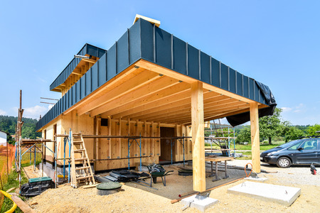 Energiezuinig passief houten huis bouwen. Bouwplaats en buitenkant van een houten paneelhuis met steigers klaar voor muurisolatie.