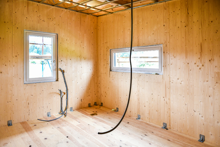 attic: Building energy efficient passive wooden house. Construction site and interior of a wooden panel house with scaffolds ready for wall insulation and different installations.
