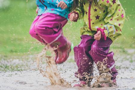 Kinder in Gummistiefeln und Regenkleidung springen in Pfütze. Wasser spritzt von Mädchenfüßen, während sie springt und im Regen spielt. Schützende Gummi-Hose und Jacke zum Spielen im Schlamm.