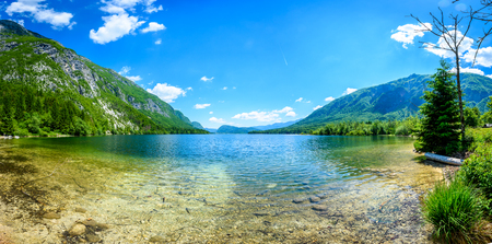 bohinj: Amazing beautiful lake Bohinj in Slovenia view from Ukanc. Mountain alpine lake Bohinj surrounded by mountains in Triglav national park Slovenia with calm water on a sunny day.