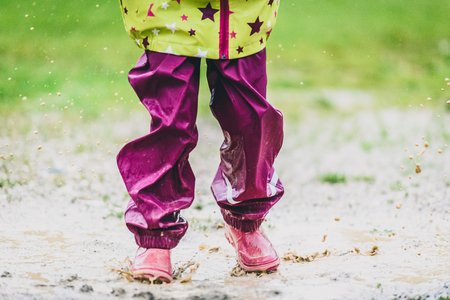 muddy: Children in rubber boots and rain clothes jumping in puddle. Water is splashing from girls feet as she is jumping and playing in the rain. Protective rubber pants and jacket for playing in the mud. Stock Photo