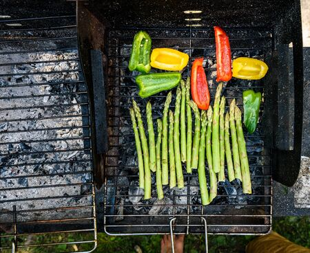 vegtables: Asparagus and bell peppers on a barbecue bbq charcoal grill. Delicious vegan barbecue outdoors picnic meal. Grilling vegetables for vegetarians or vegans. Stock Photo