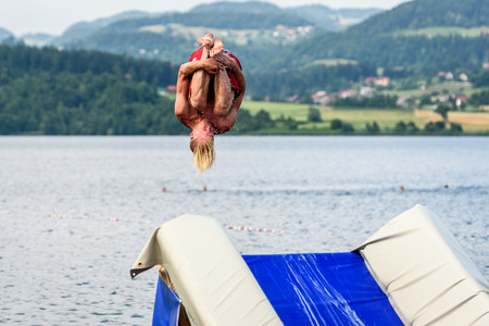 skate park: Velenje, Slovenia - June 24, 2017: Pljusk na Velenjski plazi extreme sports lake jumping competition event. Different extreme activities including slip and slide, bike, skate and roller ramp jumping in the lake.