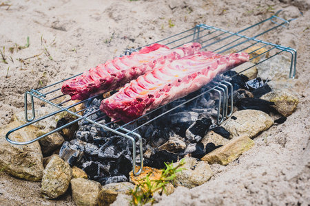 Making pork ribs on homemade improvised BBQ barbecue grill.