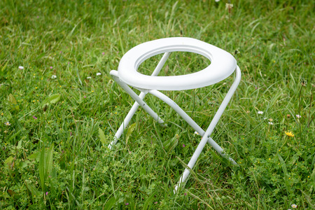 Portable Folding Camp Toilet outdoors in the grass. Camping or motor home toilet accessories for camping in the nature. Stock Photo