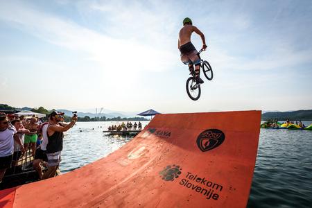 Velenje, Slovenia - June 24, 2017: Pljusk na Velenjski plazi extreme sports lake jumping competition event. Different extreme activities including slip and slide, bike, skate and roller ramp jumping in the lake.