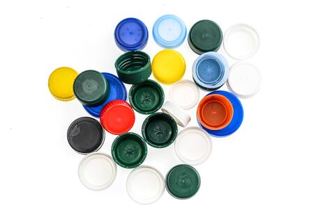 Plastic bottle caps in different colours. A pile of plastic bottle covers. Isolated on white background. Stock Photo