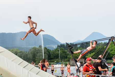 mtb: Velenje, Slovenia - June 24, 2017: Pljusk na Velenjski plazi extreme sports lake jumping competition event. Different extreme activities swing jumping in the lake by Dunking Devils Editorial