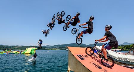 Velenje, Slovenia - June 24, 2017: Pljusk na Velenjski plazi extreme sports lake jumping competition event. Different extreme activities including slip and slide, bike, skate and roller ramp jumping in the lake. Stock Photo - 81588457