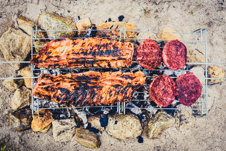 Pork ribs and burgers on homemade improvised BBQ barbecue grill. Making Churrasco  on coal, fire, briquettes BBQ grill in the sand with rocks stones Camping and charcoal grilling ideas life hacks.
