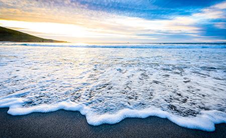 日の出日の入りで砂浜に小さな海海の波。干潮時に小さな波で大西洋のビーチで夕暮れや夜明けの背景風景画像。背景の壁紙画像。 写真素材