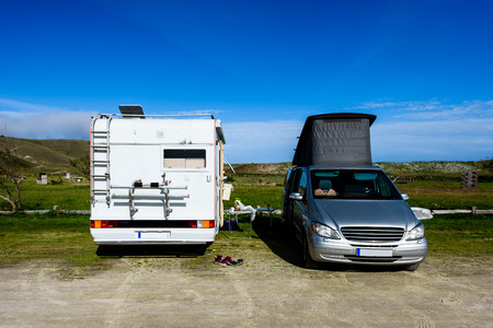 Motorhome RV and campervan are parked on a beach. Two motor home caravans are parked on a parking space for RV vehicles in Galicia - Spain.