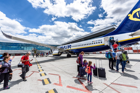 SANTIAGO DE COMPOSTELA, SPAIN - MAY 19, 2017: Passengers boarding Ryanair flight from Santiago Spain to Milano Italy on a sunny day. Ryanair is biggest budget low-cost airline in the world.
