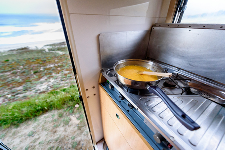 Cooking dinner or breakfast in camper RV with beach view. Preparing eggs with magnificant view of Nemiña beach Galicia Spain. Traveling with RV, motor home caravan or motorvan.