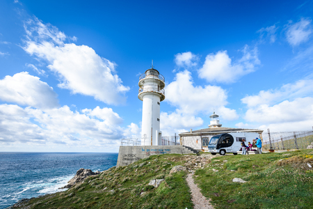 CABO TOURINAN, SPAIN - MAY 17, 2017: Tourists with RV motorhome camper at Cabo Tourinan - the most western point of Spain with lighthouse. Popular tourist and pilgrim destination.  Beautiful old lighthouse on rocky cliff and Atlantic ocean in Spain.