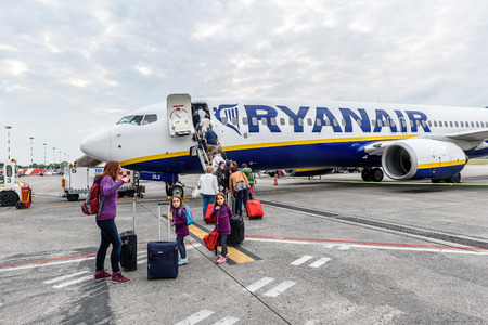 Milano, Italy - MAY 10, 2017: Passengers boarding Ryanair flight from Milano Italy to Santiago de Compostela Spain on a cloudy day. Ryanair is biggest budget low-cost airline in the world.