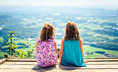 Bambini - ragazze gemelle sedute sulla rampa di parapendio dopo un'escursione. Famiglia attiva, genitori e bambini alpinisti nella natura. I bambini riposano e godono di una vista su Lubiana da Smarna gora. Archivio Fotografico - 85646897