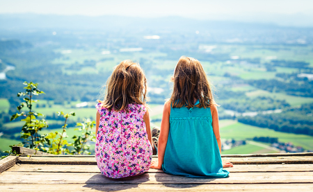 Children - twin girls sitting on paragliding ramp after hiking. Active family, parents and children mountaineering in the nature. Kids are resting and enjoying a view of Ljubljana from Smarna gora.